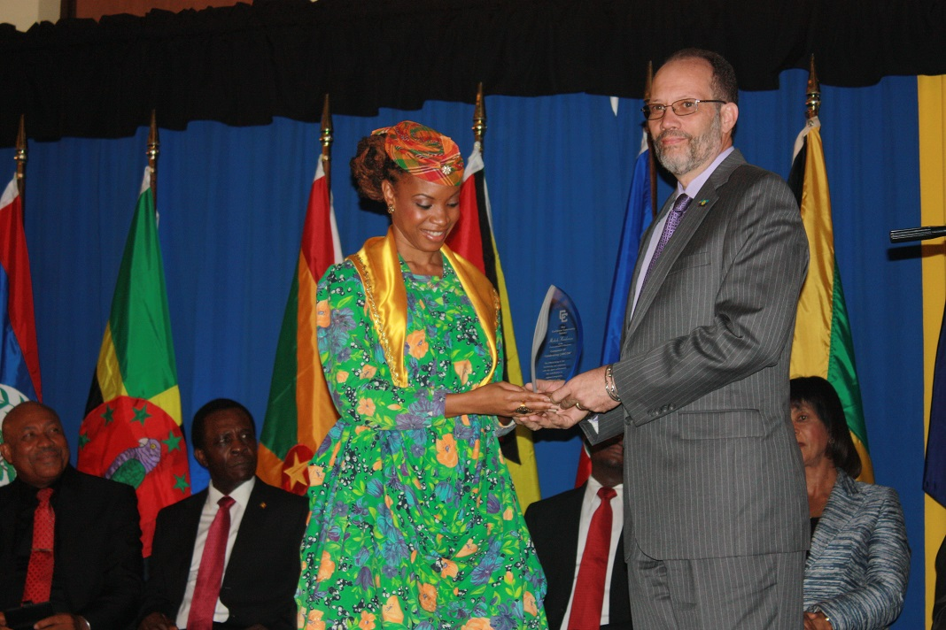 Winner of the CARICOM Song Competition Michele Henderson accepts her award from Secretary General of the Caribbean Community Ambassador Irwin LaRocque