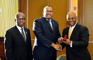 New CTO Chairman Obie Wilchcombe of the Bahamas (right) receives the gavel from his predecessor Richard Sealy of Barbados. Also in photograph, CTO secretary general Hugh Riley (Right) (Photo via CTO)