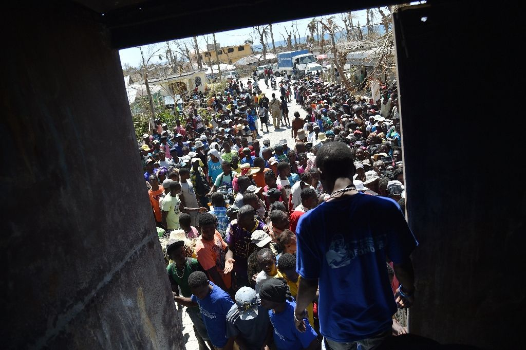 Hurricane Matthew victims wait to receive food from the UN's World Food Programme in Roche-a-Bateaux, in Les Cayes, in the south west of Haiti, on October 12, 2016 Hurricane Matthew victims wait to receive food from the UN's World Food Prog