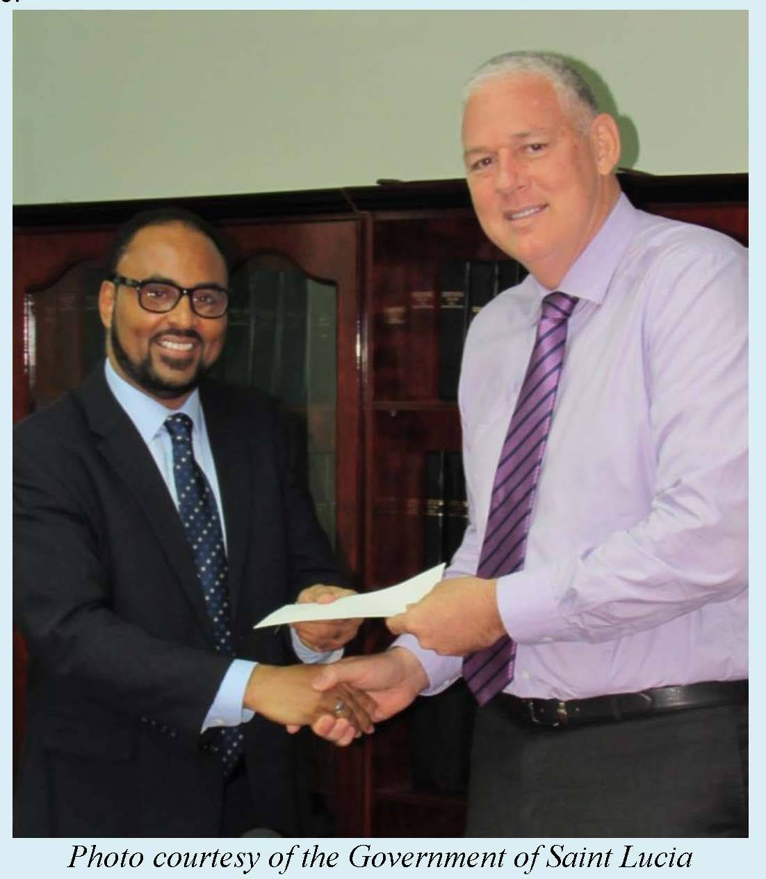 Saint Lucia's Prime Minister Hon. Allen Chastanet receives a cheque from CCRIF CEO Mr. Isaac Anthony