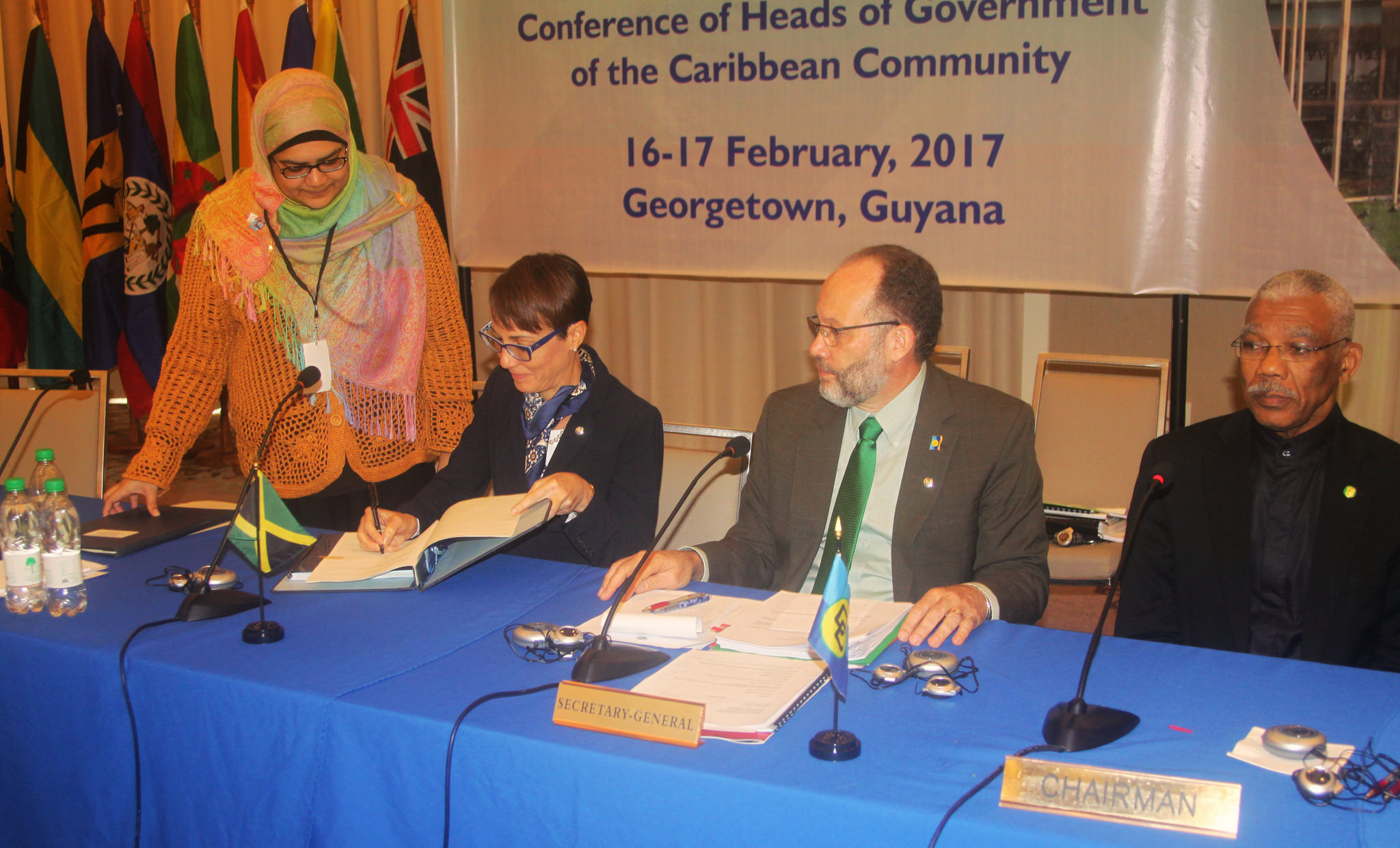 Senator The Hon. Kamina Johnson-Smith, Minister of Foreign Affairs and Foreign Trade of Jamaica, signing the Amendment to the CDF Agreement, while CARICOM Secretary-General Ambassador Irwin LaRocque looks on