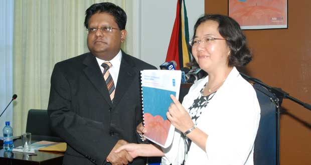 Minister of Finance, Dr. Ashni Singh, officially receives the 2014 Human Development report from Resident Representative, UNDP, Chisa Mikami (Photo Credit Guyana Chronicle)