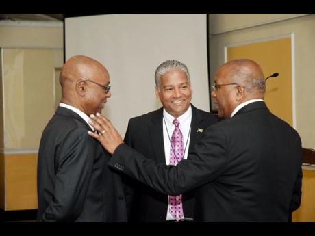 Dr Morais Guy (right) in discussion with the chairman of the Jamaica Civil Aviation Authority (left), B. St Michael Hylton; and Director General of the Jamaica Civil Aviation Authority Nari Williams-Singh during the three-day meeting held at the Terr