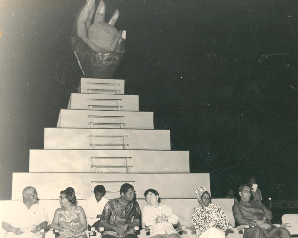 At the closing ceremony of CARIFESTA 1972 is the CARIFESTA logo – a dark hand grasping the sun, depicting the skills and aspirations of the tropical man with talent untold'. In the foreground are (second and third from left respectively)