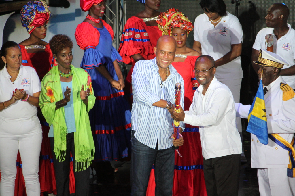 President of Haiti, H. E. Michel Martelly hands over the CARIFESTA baton created by acclaimed Haitian Visual Artist Phillipe Dodard to Barbados Minister of Culture Hon. Stephen Lashley