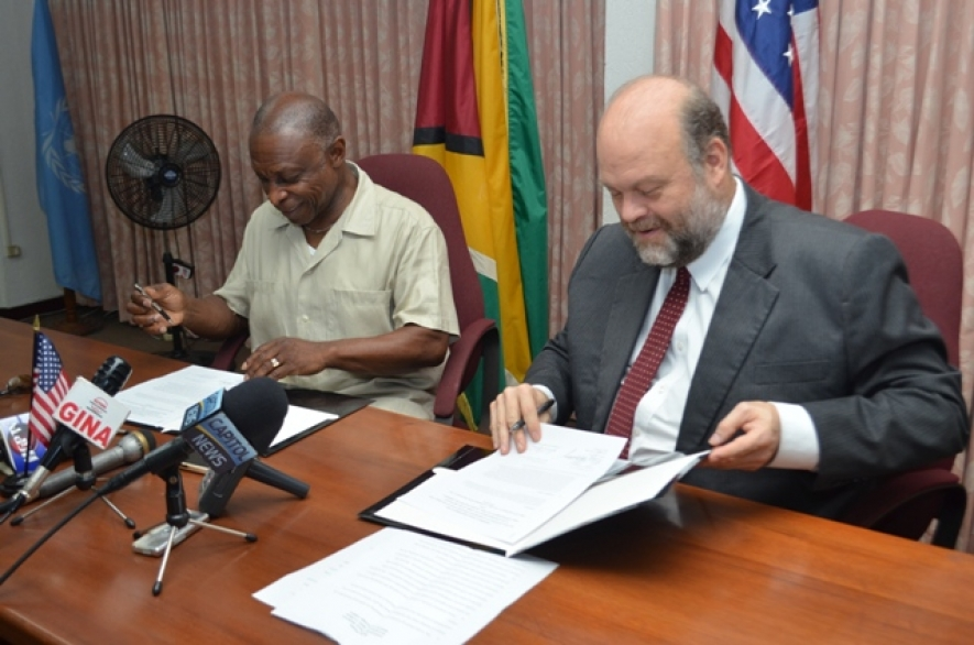 """Minister of Foreign Affairs and Vice President Carl Greenidge and US Ambassador Perry Holloway, affixing their signatures to the Caribbean Basin Security Initiative's (CBSI's) """"Letter of Amendment Three Point Two,"""" in the Main"""