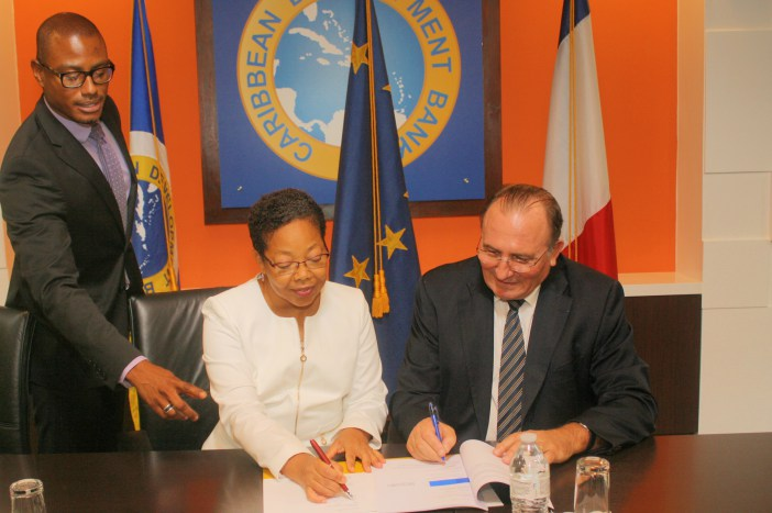 Patricia McKenzie (centre), CDB Vice-President, Operations and Eric de la Moussaye (right), French Ambassador to the Organisation of Eastern Caribbean States and Barbados, sign the Credit Facility Agreement. Looking on is Dave Waithe, Legal Counsel a