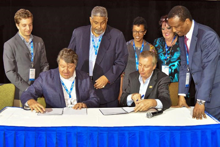 Director General and CEO of CHTA Frank Comito (seated at right) and USAID CARCEP's Energy Efficiency Promotion Specialist John Marcocchio at yesterday's signing in Puerto Rico. Standing from left is Jonathan Schwartz of Deloitte Consultin