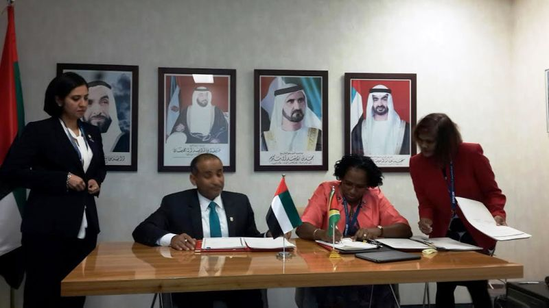 Minister Ferguson signing the agreement with an UAE official.