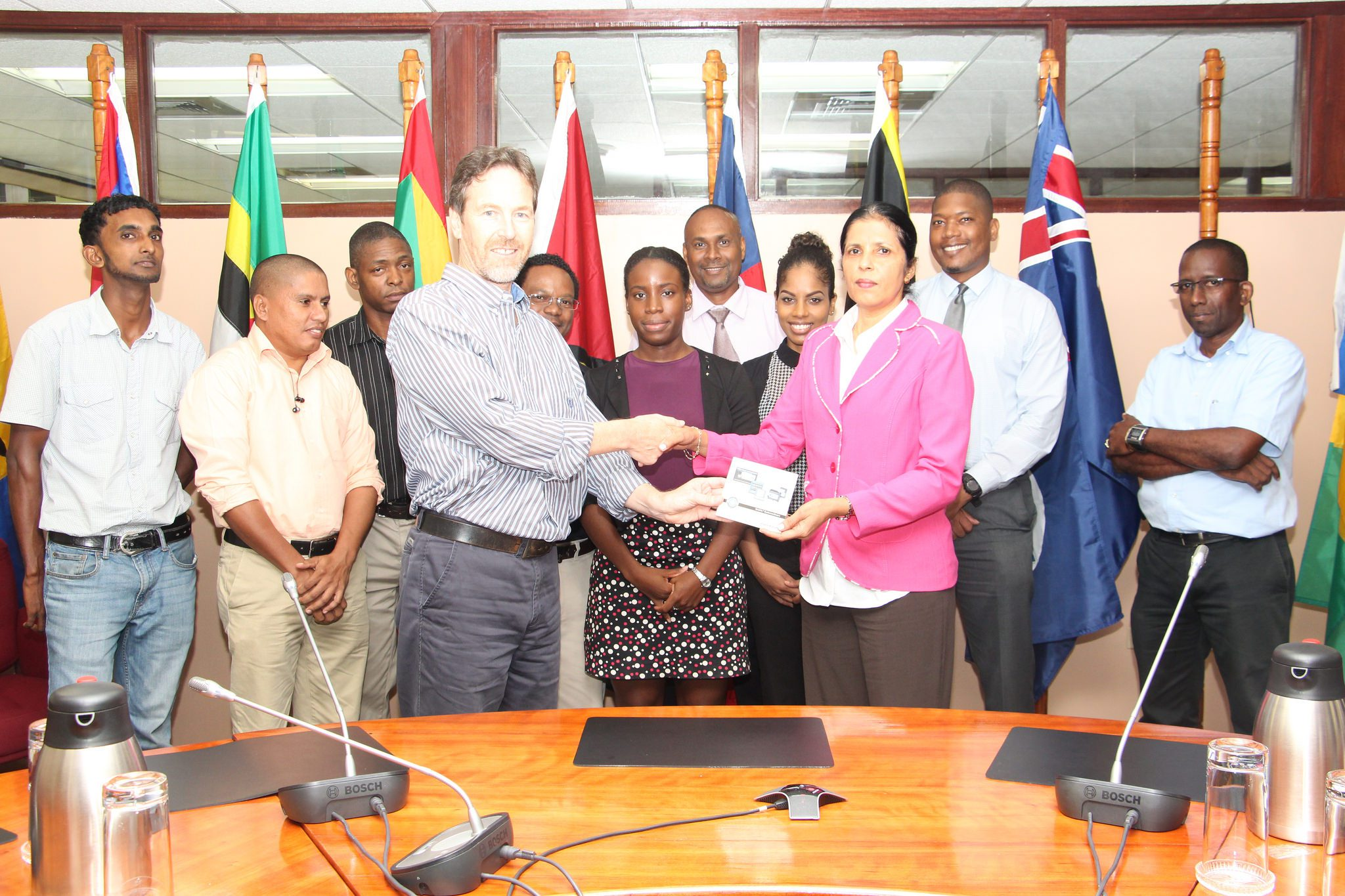 Mr. Glynn Morris of the GIZ/REETA Programme hands over the software to CARICOM DSG, Amb. Manorma Soeknandan PhD., in the presence of other CARICOM Secretariat staff members