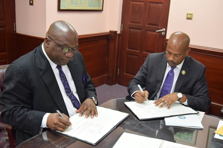 Prime Minister Dr. the Hon. Timothy Harris and CDF CEO Mr. Rodinald Soomer sign CDF agreement (Photo via SKNIS)