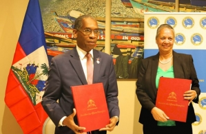 Haiti's Minister of Foreign Affairs, His Excellency Antonio Rodrigue (left) and Vice-President (Operations), Caribbean Development Bank (CDB), Monica La Bennett (right), hold the signed country agreements after signing them on February 27, 2018