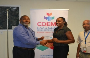 Philmore Mullin, Director of NODS, Antigua & Barbuda and Brigadier General (Rtd) Earl Arthurs, Consultant with the CDEMA CU captured above presenting a Grocery Voucher to Salome Deazle.