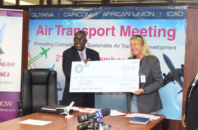 General Manager, SOL Aviation Guyana, Liz Wyatt hands over a cheque for $1M to Franklin 'Bobby' Vieira, Director of Marketing and Operational Support on Friday (DPI)