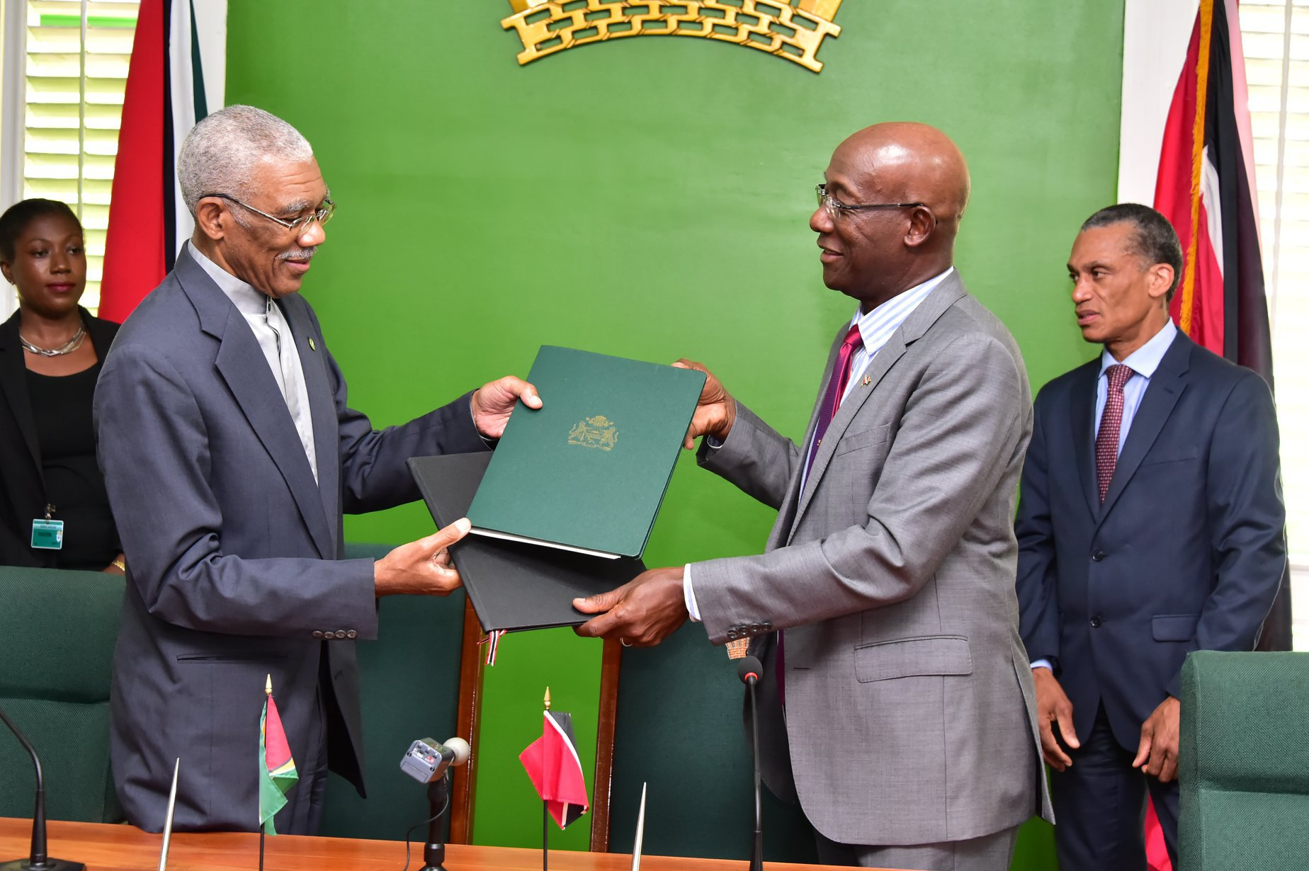 President David Granger and Prime Minister Keith Rowley exchange copies of the MOU (Photo via Ministry of the Presidency)
