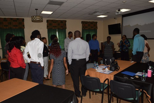 Staff members turn their attention to Mrs. Gray-Phillip as she interacts with them during an icebreaker session. (Photo via SKNIS)