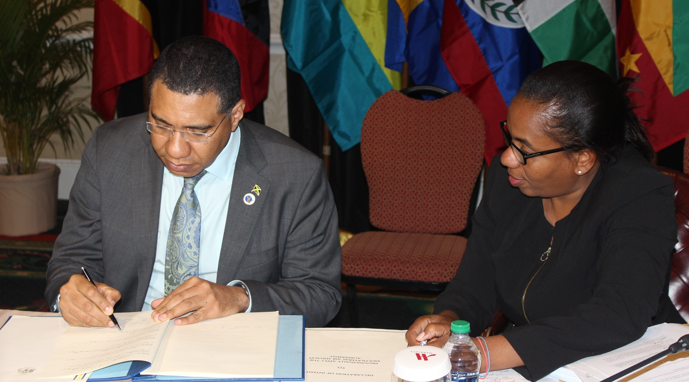 Prime Minister Andrew Holness signing