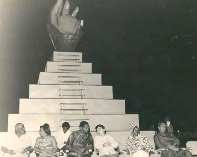 At the closing ceremony of CARIFESTA 1972 is the CARIFESTA logo – a dark hand grasping the sun, depicting the skills and aspirations of the tropical man with talent untold'. In the foreground are (second and third from left respectively) then Prime Minister of Guyana, Linden Forbes Sampson Burnham and then President of Guyana, Arthur Chung.
