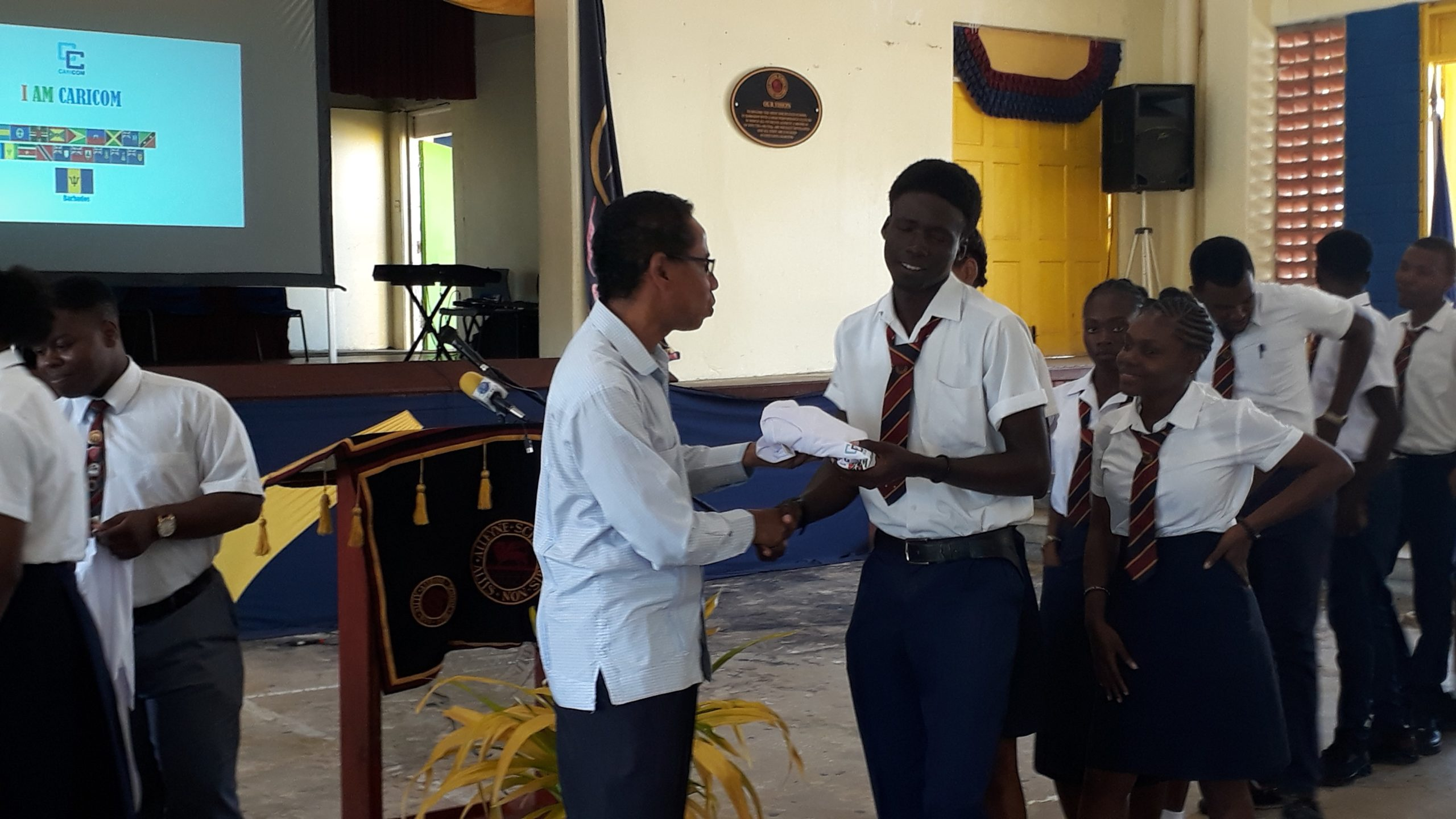 Ambassador Comissiong presenting an 'I Am CARICOM' T-shirt to a student during the launch